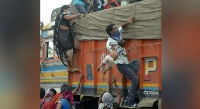 Photo of man hauling baby onto a truck depicts plight of stranded workers in India