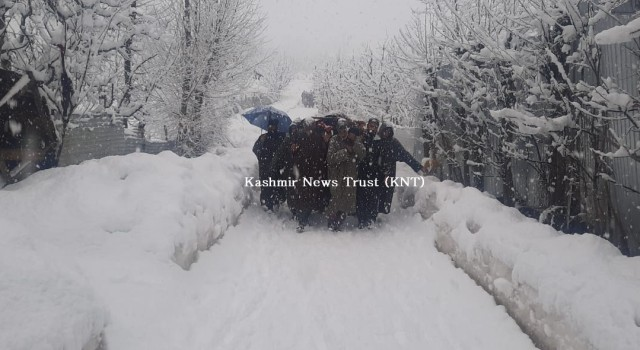 Amid snowfall, local Muslims walk on foot to shoulder the dead body of a Pandit stuck in an ambulance in Shopian